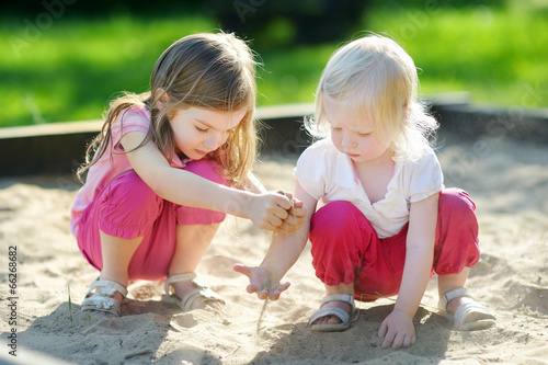 Photo  Two little sisters playing in a sandbox