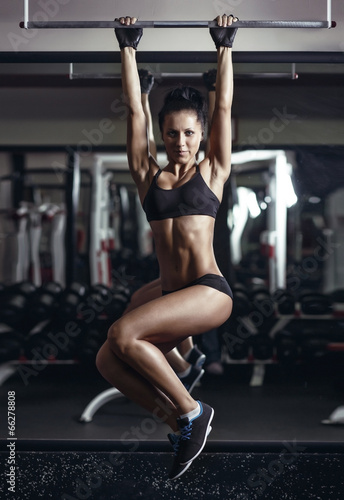 Brunette sexy young fitness girl pulls up in the gym