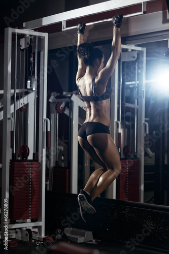sexy young fitness brunette woman pulls up in the gym