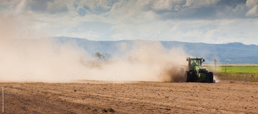 Fototapeta Tractor plowing dry farm land