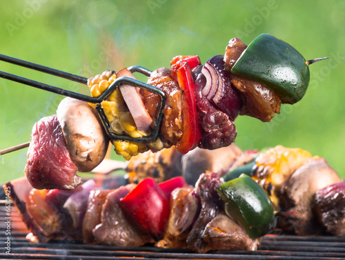 Valokuva  Tasty skewers on garden grill, close-up.