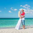 Loving couple at sunny sea beach with red heart