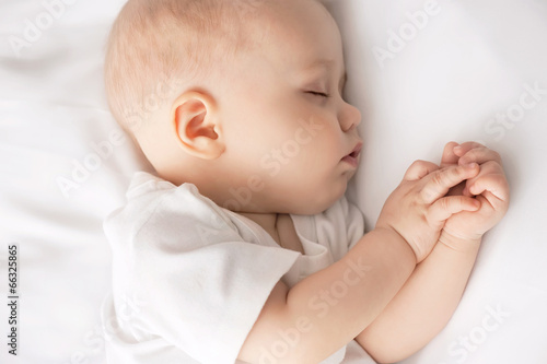 Carefree sleep little baby with a soft toy on the bed Canvas Print