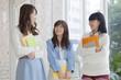 ノートを持って友達と会話をする女子学生