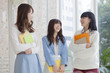 ノートを持って友達と談笑する女子学生