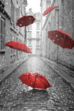 Fototapeta Uliczki - Red umbrellas flying on the street. Conceptual image