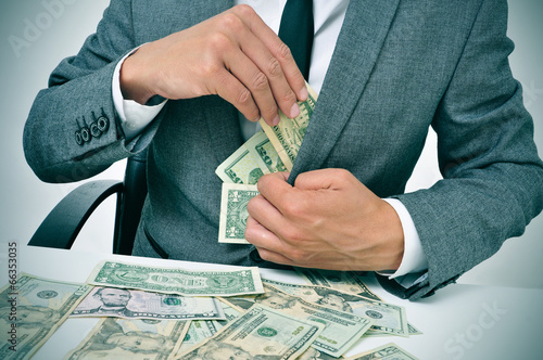 Fotografia, Obraz man in suit getting dollar bills in his jacket