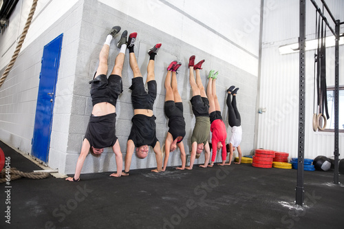 Team exercising handstands at fitness gym center Fototapeta