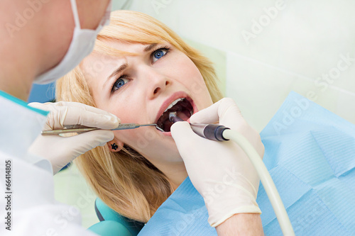 Fotografering  Female patient in dentist office getting oral exam, procedure