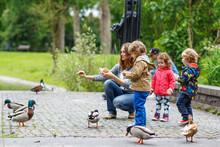 Mother And Her Children Feeding Ducks At Summer