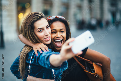 Fotomural Multi ethnic Friends having fun in city taking selfie