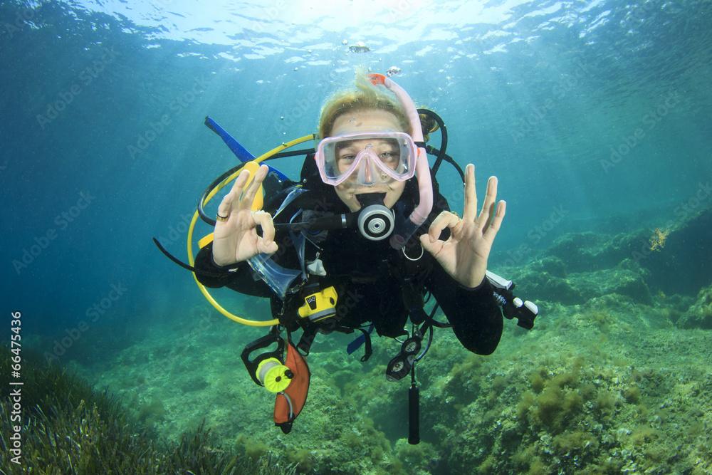 Fototapeta Young woman scuba diving signals okay
