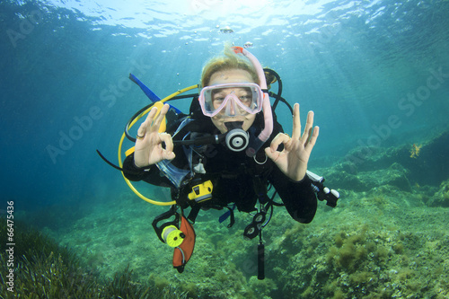 Fotobehang Duiken Young woman scuba diving signals okay