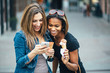canvas print picture - Multi ethnic Friends eating ice cream in city and texting