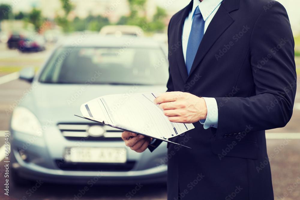 Fototapeta man with car documents outside