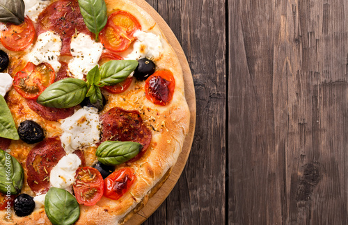 Fotografia  Rustic pizza with salami, mozzarella, olives and basil on wooden