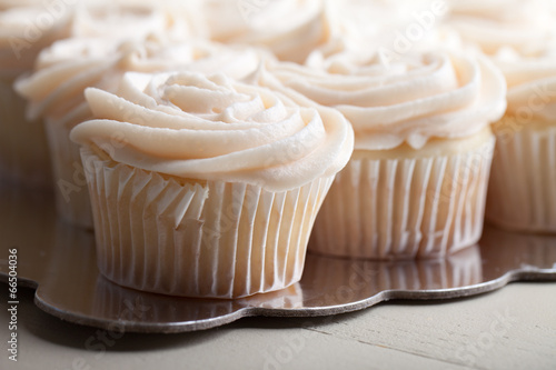 Foto Gourmet strawberry filled cupcakes with white chocolate frosting - side view