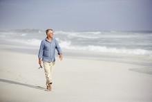 Senior Man Walking On Beach