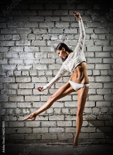 Photo  Young dancing woman on brick wall (dark version)