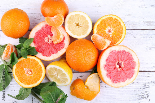 Canvas Fresh citrus fruits with green leaves on color wooden
