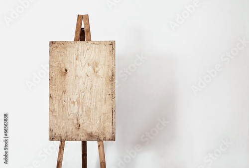Photo  Blank grunge easel in a light room