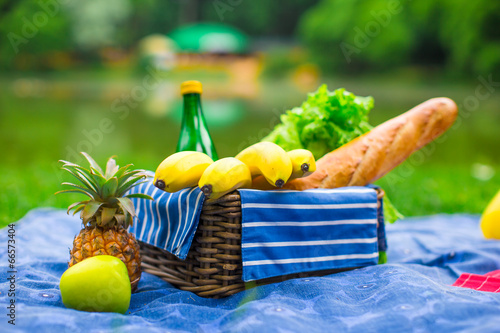 Aluminium Prints Picnic Picnic basket with fruits, bread and bottle of white wine