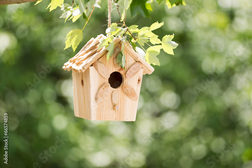 Photo New Wooden Birdhouse hanging on tree branch outdoors