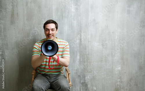 Obraz na plátne man sitting on a chair holding a megaphone and cute smiles on a