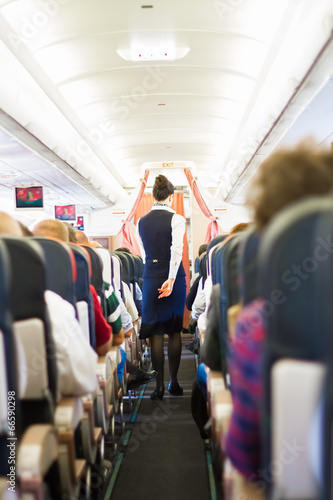 Tuinposter Interior of airplane with passengers on seats.