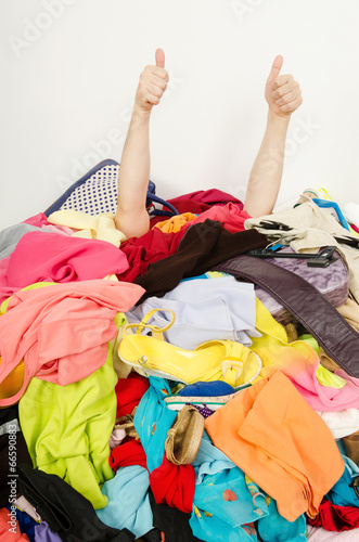 Fotografia, Obraz  Man hands signing thumbs up reaching from a big pile of clothes