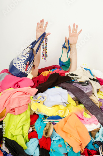 Valokuva  Man hands reaching out from big pile of clothes and accessories,