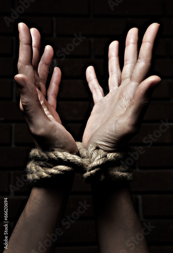 Canvas Print Tied hands on dark background