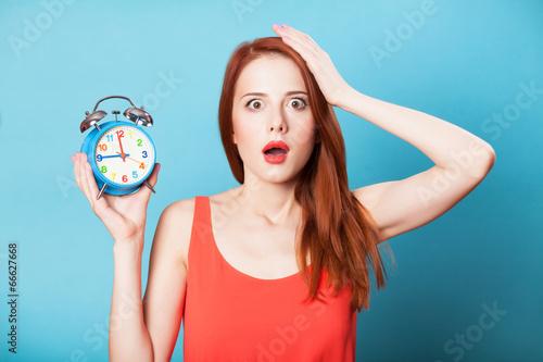 Fotografie, Obraz  Surprised redhead women woth alarm clock on blue background.