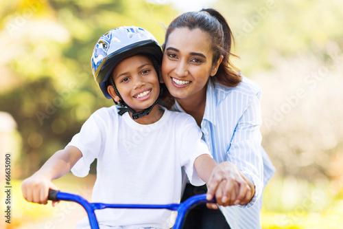 Carta da parati indian mother teaching her son to ride a bike