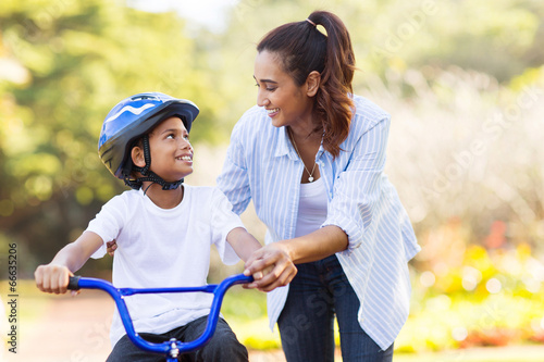 Photo mother help her son ride a bicycle