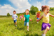 canvas print picture Excited running kids in green field play together