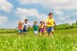 canvas print picture Running kids in green field during summer