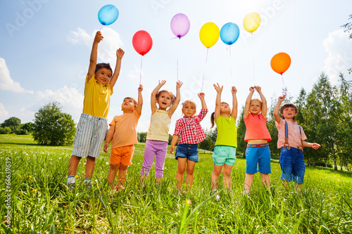 canvas print motiv - Sergey Novikov : Happy kids with balloons and arms up in the sky