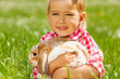 canvas print picture Cute girl cuddling rabbit in green field