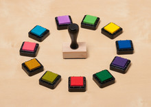 Rubber Stamp And Set Of Ink Pads On Wooden Desk