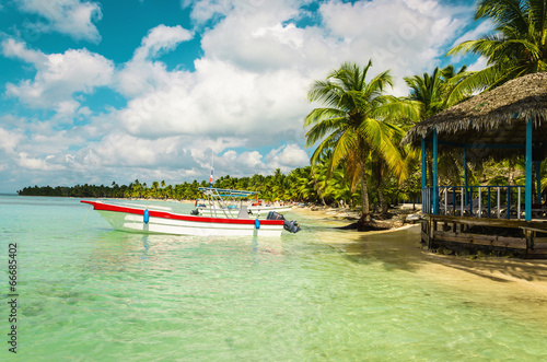 Foto  Boat moored off the coast of the island full of palm trees