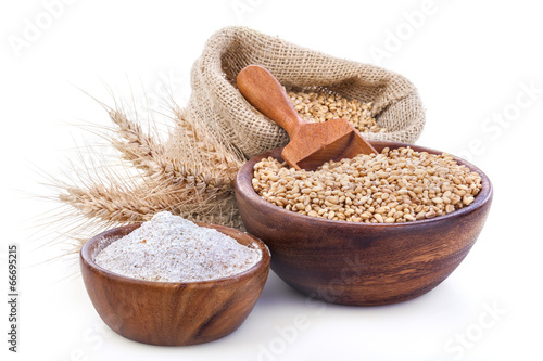 Ripe wheat and flour in a wooden bowls