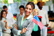 Cheerful businesswoman holding flag of USA