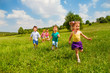 canvas print picture Running children in green field during summer