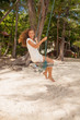 girl playing the swing on beach