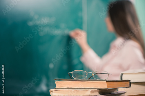 Fototapeta glasses and books with teacher writing at blackboard