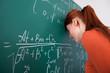 Student Leaning Head On Blackboard In Classroom