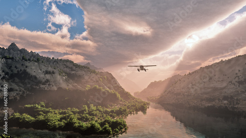 Poster Cappuccino Small airplane flying through snow mountain valley with river. C