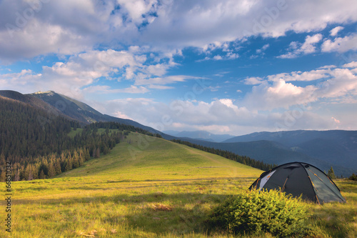 In de dag Kamperen Camping tent in the mountains. Summer, blue sky, clouds and high