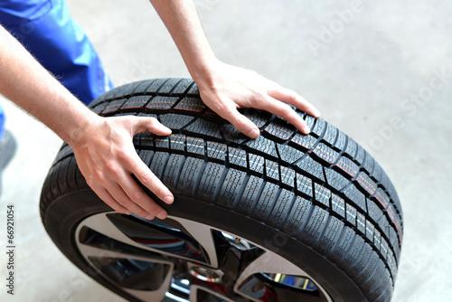 Fotografiet  Reifenwechsel in einer KFZ Werkstatt // Tire change by mechanic